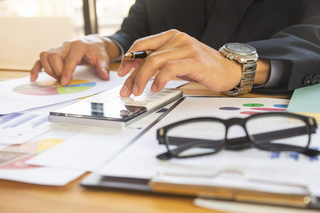 Business man in office and calculate financial plan sales. Working on desktop computer making business plan, business investment advisor consulting on the financial report, plan a marketing plan at business office. Business accounting plan concept.