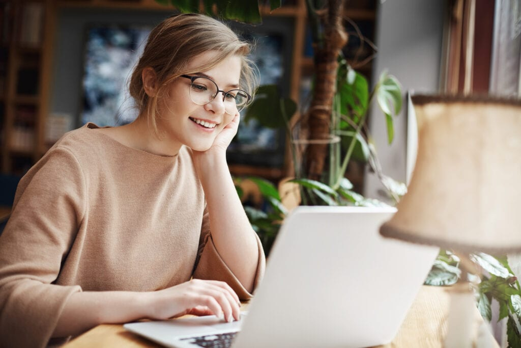 Cheerful young caucasian girl in glasses using laptop, shopping online or browsing internet, chatting with friends, edit photos for university project, smiling as looking computer screen
