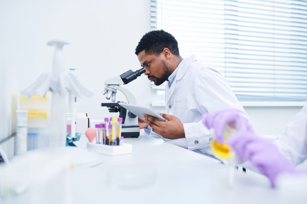 Side view of African-American lab technician looking into microscope wearing lab coat