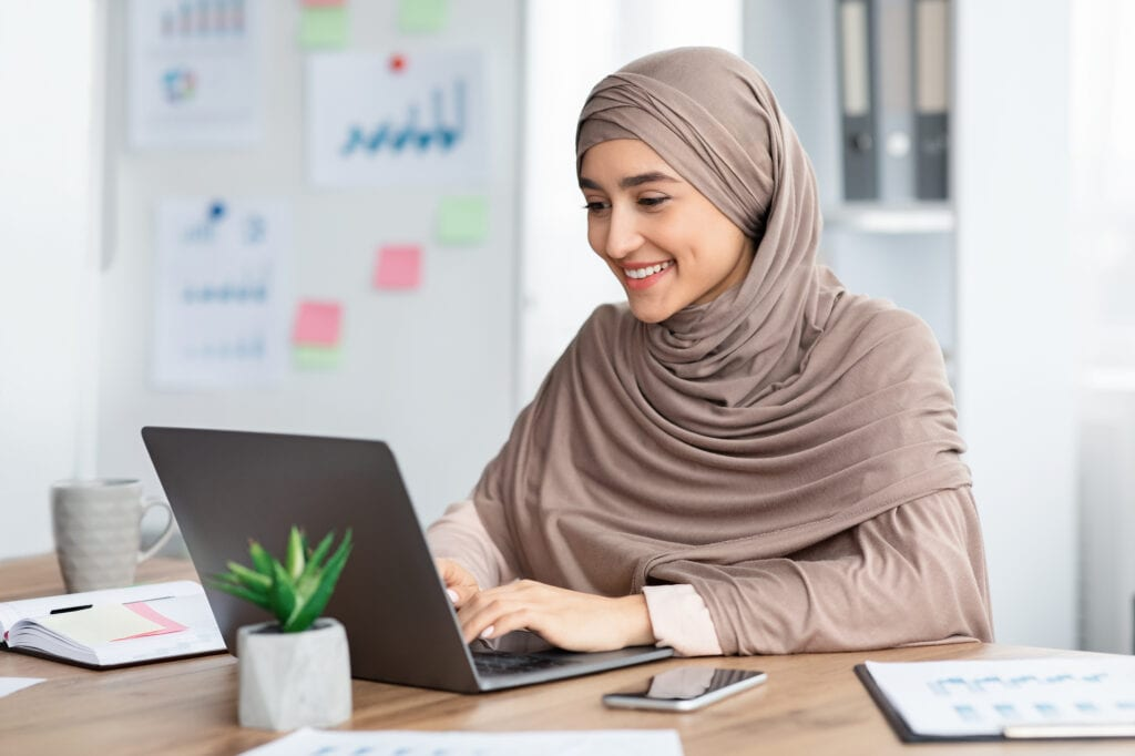 Office Job. Happy islamic woman in hijab working on laptop at desk, typing on keyboard and looking at computer screen.