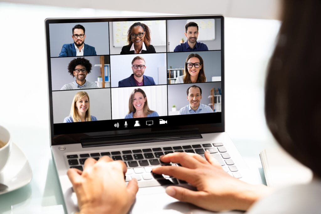 woman having videoconference with nine people on laptop screen